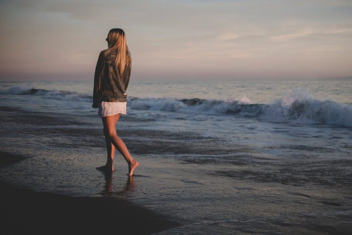 woman walking beside seashore